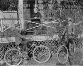 Two Boys on Bicycles with a Woman sitting on the Porch