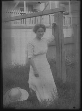 Woman leaning against a Wooden Post