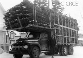 Roland Blair standing next to Herb Lassenba's truck delivering Christmas Trees