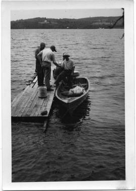 Group of men on a dock and canoe
