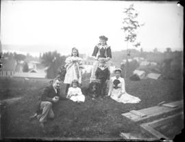 Man, woman, 3 children and a dog on a hill