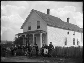 Group stands in front of house with bicycles