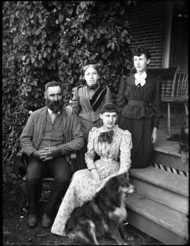 A man, 3 women and a dog sitting on a stoop
