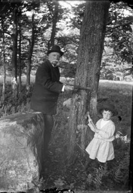 Man and child chopping tree
