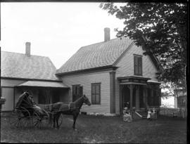 Horse drawn buggy in front of house